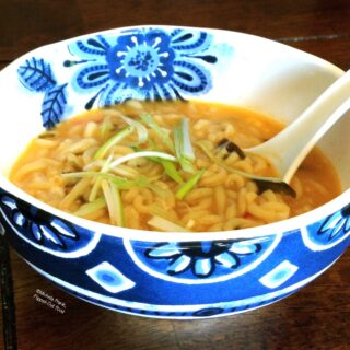 Ramen soup in a decorative blue and white bowl. The ramen is garnished with slivered scallions.