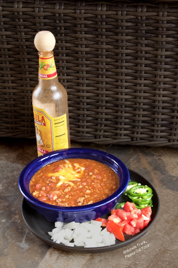 Quick, Easy Turkey Chili topped with Colby-Jack cheese in a blue bowl on top of a plate with chopped onions and tomatoes and sliced jalapenos. A bottle of Cholula sits in the background.