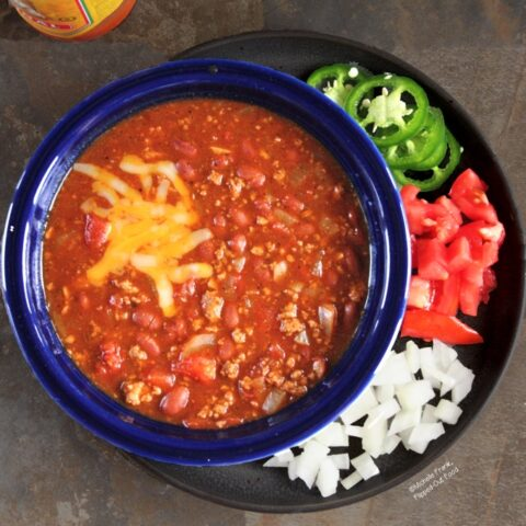 Quick, Easy Turkey Chili topped with Colby-Jack cheese in a blue bowl on top of a plate with chopped onions and tomatoes and sliced jalapenos.