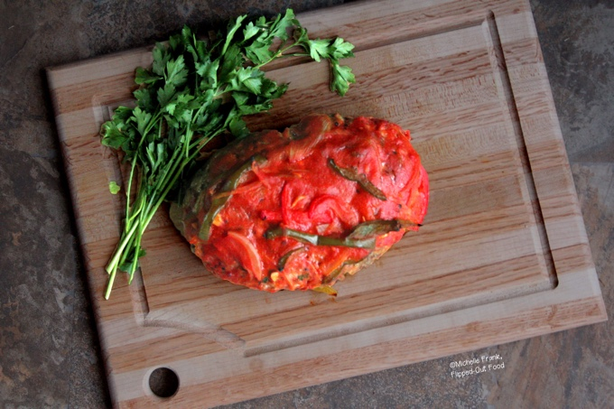 Mediterranean-Style Meatloaf topped with a tangy onion-pepper sauce, sitting atop a cutting board next to a bunch of parsley.