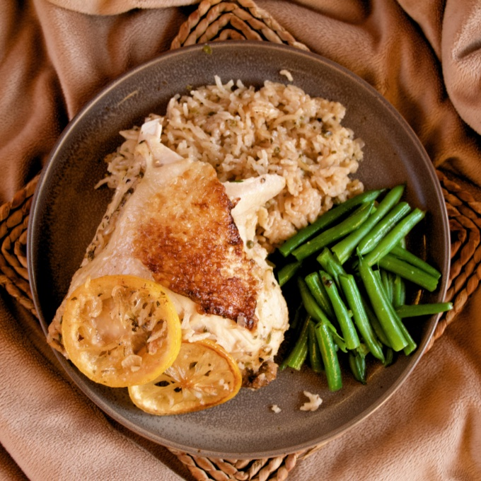 One-Pan Meyer Lemon Chicken and Rice on a plate with a side of green beans.