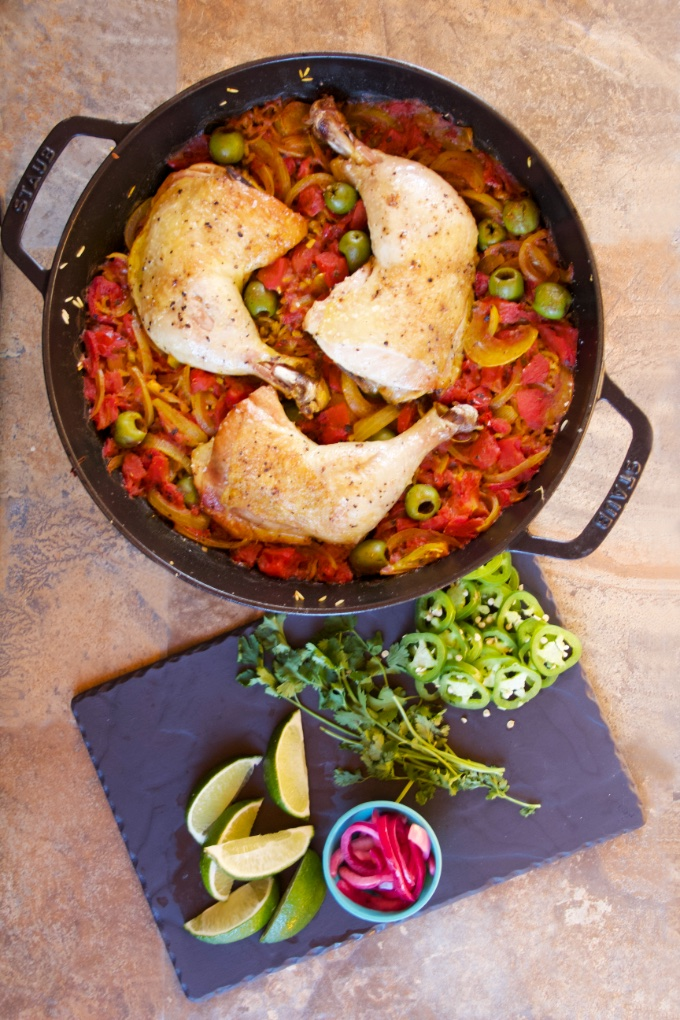 One-Pan Arroz con Pollo: the finished chicken in the skillet with the rice. A slate-grey platter of garnishes sits next to the skillet.