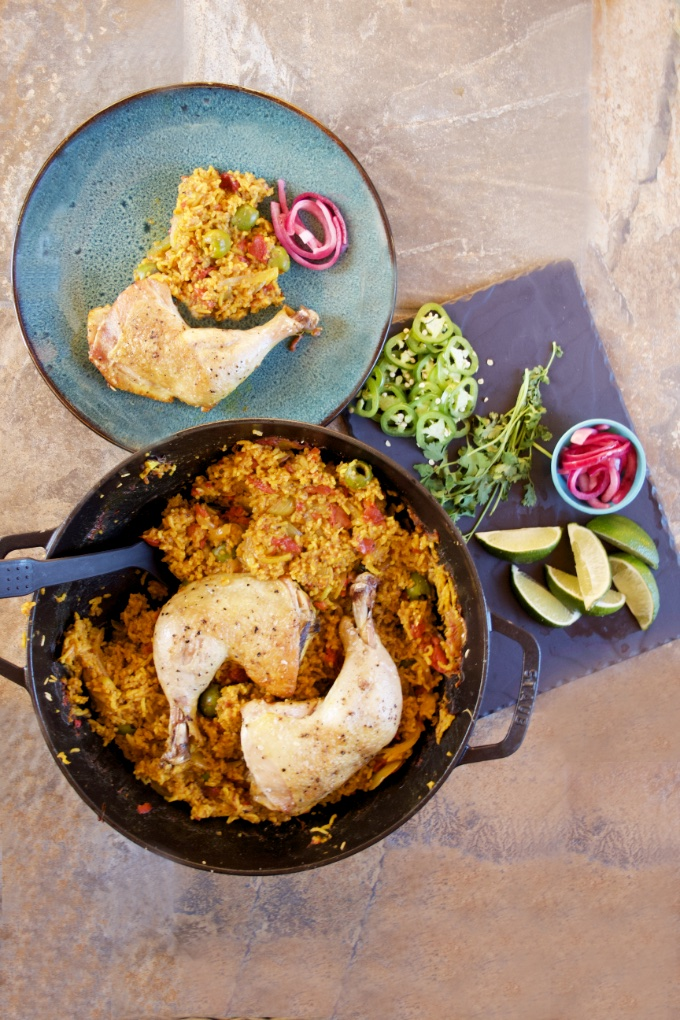 One-Pan Arroz con Pollo: Side view of a serving of arroz con pollo, rice, and pickled onion on a blue stoneware plate. The skillet has a serving scooped out. A slate platter of garnishes sits nearby with cilantro, sliced limes, and ruby-red pickled onion.