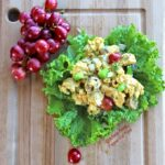 Curried Chicken Salad on lettuce leaves with a bunch of grapes. An easy party or picnic recipe, great in lettuce or flatbread wraps—or on buttery croissants. #currychickensalad #curriedchickensalad #partyfood #picnicfood #chickensalad #flippedoutfood #healthyeating via @FlippedOutFood