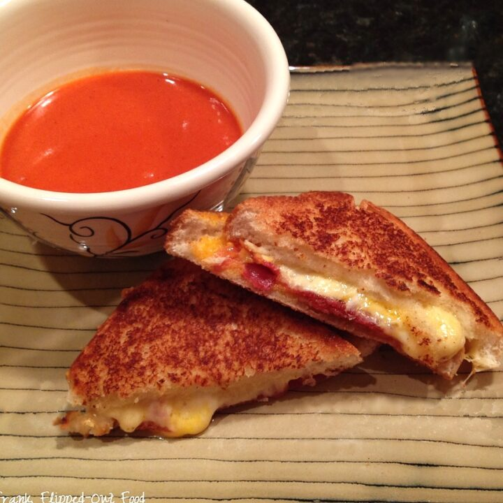 roasted tomato soup and grilled cheese sandwich on a stripey plate