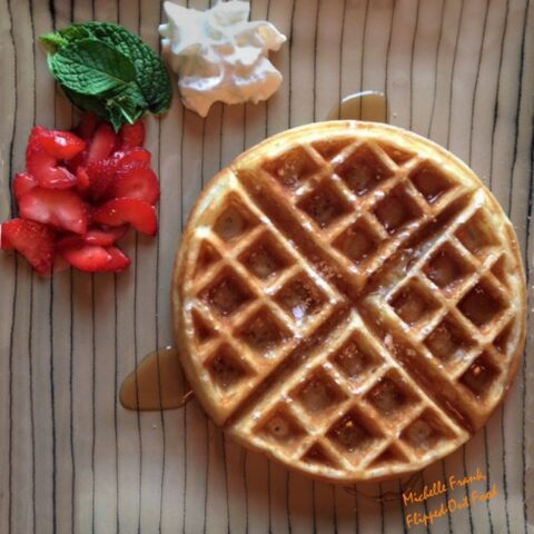 Beautiful waffle on striped plate with mint, strawberries, and whipped cream
