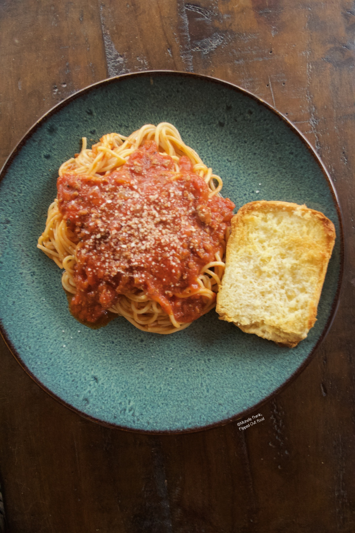 Easy Cheat Bolognese Sauce on spaghetti, served on a blue stoneware plate with a piece of garlic bread. Crumbled Romano cheese is sprinkled over the top.