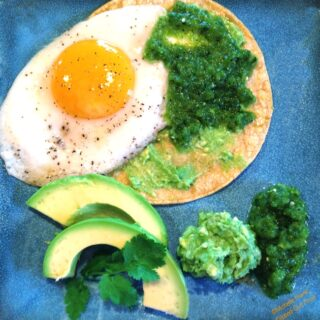 salsa verde huevos rancheros with guacamole, cilantro, and avocado slices