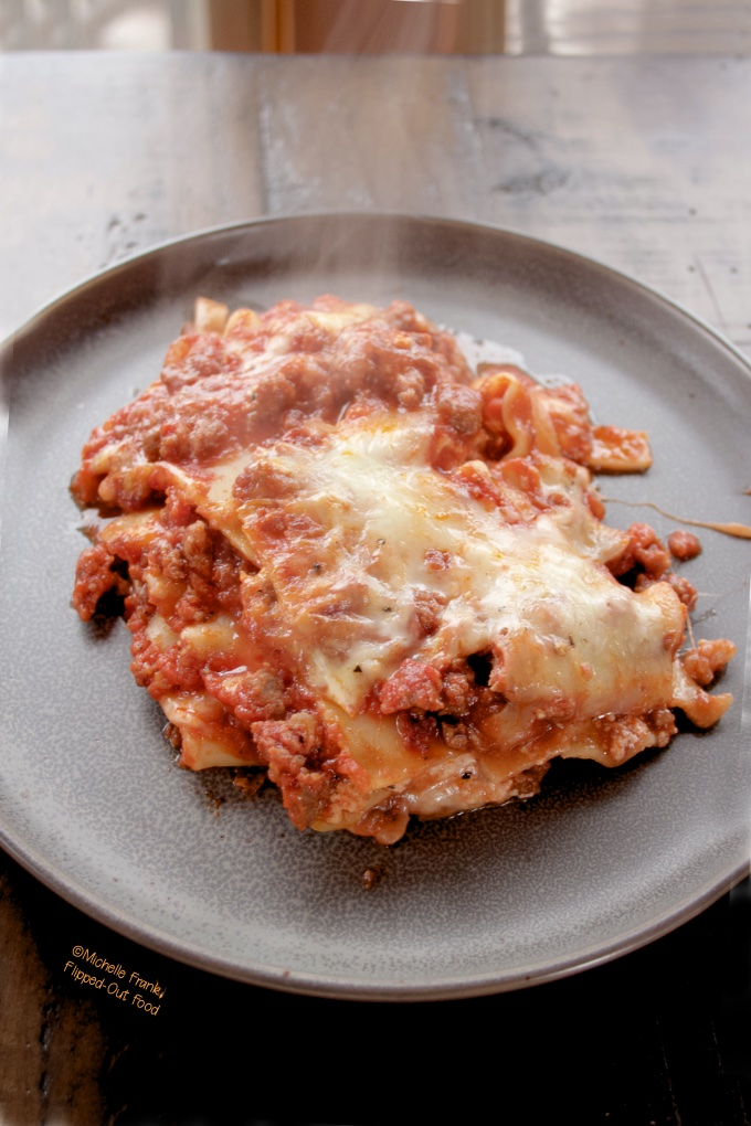 Lasagna Bolognese serving on a dark grey plate sitting on a dark, wooden table. A wisp of steam spirals up from the lasagna.