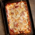 Lasagna Bolognese in a baking dish set upon a baking sheet. The lasagna is straight out of the oven and piping hot.