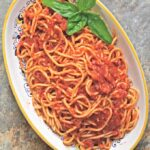 Slow-roasted tomato sauce served over spaghetti on a decorative platter with a sprig of basil.