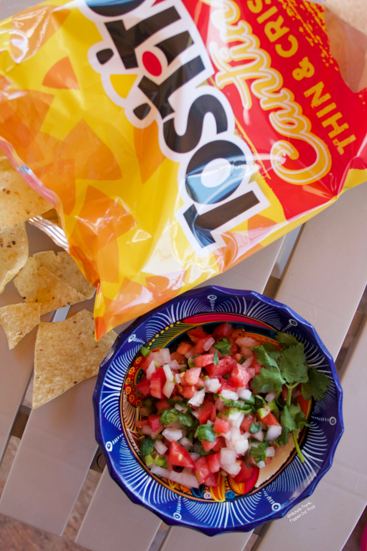 Pico de gallo in a decorative blue bowl sitting atop a patio table. The bowl sits next to a bag of tortilla chips.