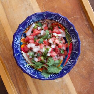 Pico de gallo in a decorative blue bowl sitting atop a wooden tray.