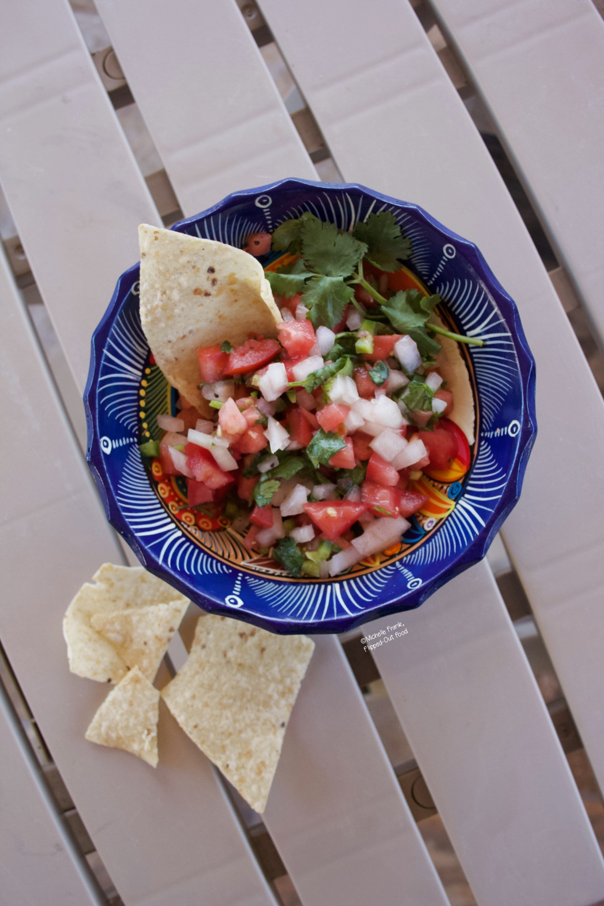 Pico de gallo in a decorative blue bowl sitting atop a patio table. A tortilla chip has been stuck into the pico de gallo, and more tortilla chips await close by.