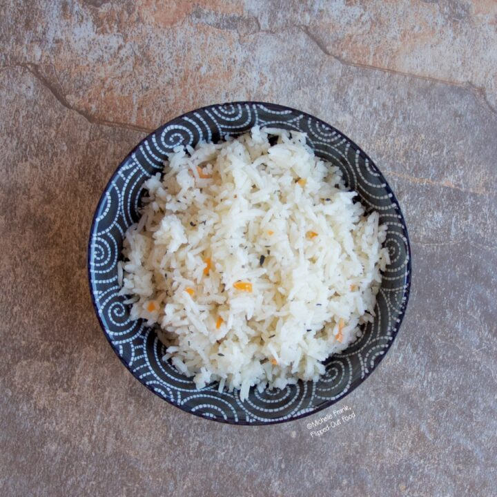 A serving of Coconut-Habanero Rice in a black bowl with white swirls.