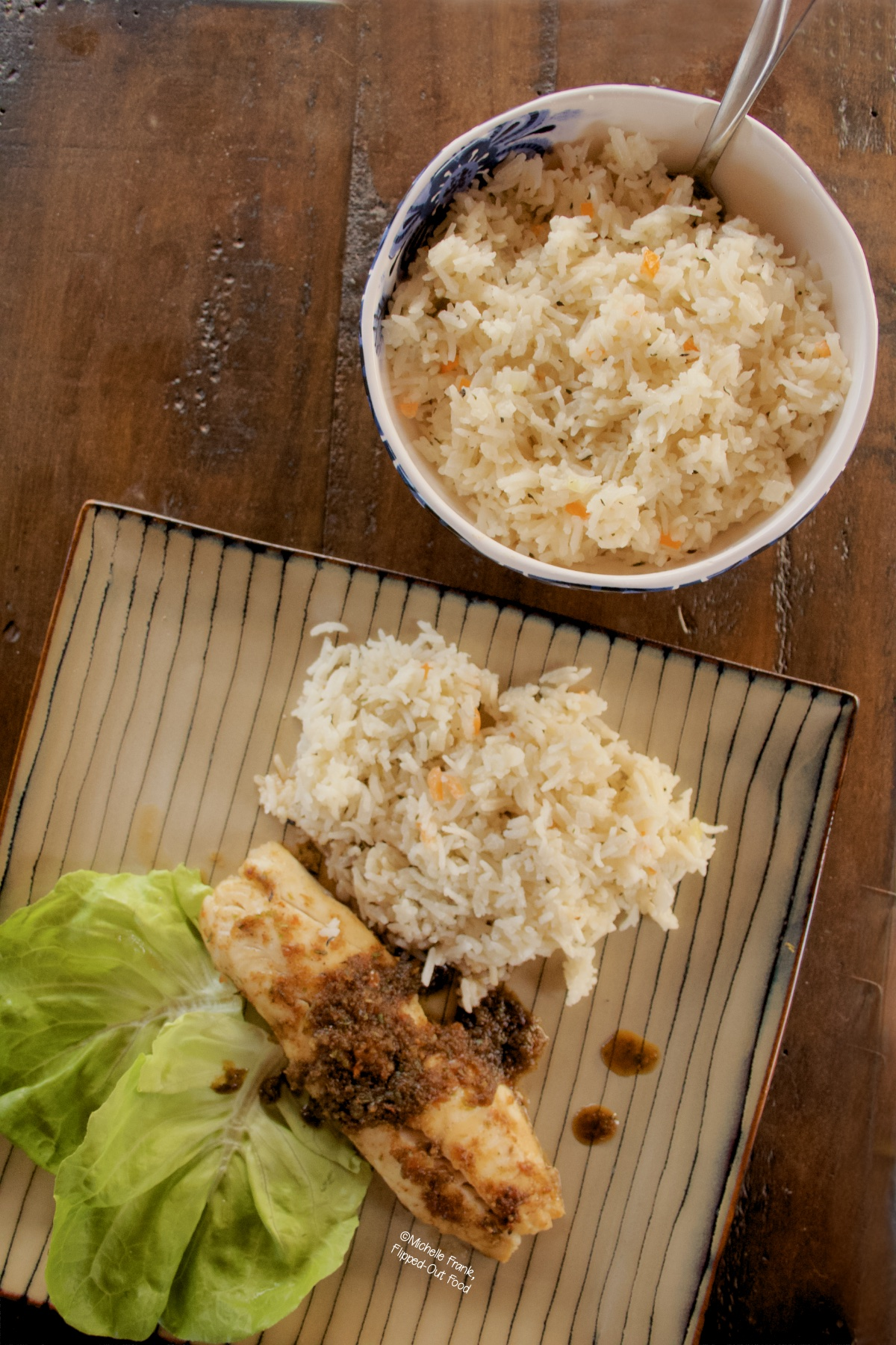 Coconut-Habanero Rice in a serving bowl next to a plate with a serving of the rice, a tilapia filet with jerk sauce, and some bibb lettuce.