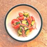 Cucumber-Tomato-Onion Salad on a white, ceramic plate with a green rim.