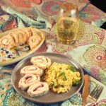 Side view of a plate with four slices of work-ahead chicken rollatini next to a serving of lemon-broccoli orzotto. In the background, a platter with slices of work-ahead chicken rollatini sits next to a glass of white wine.