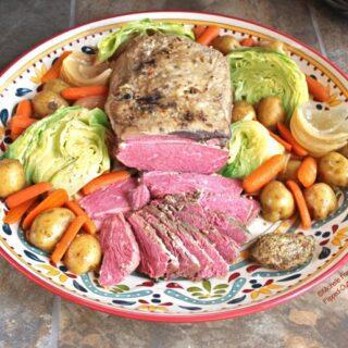 A platter of make-ahead corned beef and cabbage with a dollop of grainy mustard #irishfood #cornedbeef #cornedbeefandcabbage #saintpatricksday #comfortfood #crockpot #slowcooker