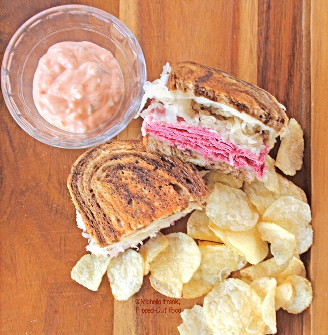 Top view of Best-Ever Reuben Sandwiches served with 1000 island dressing on the side in a clear ramekin and a serving of chips. #reubensandwich #saintpatricksday #stpaddysday #cornedbeef #pubfood #sandwich via @flippedoutfood