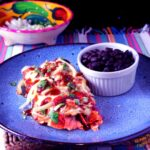 red enchiladas or chilaquiles serving with black beans