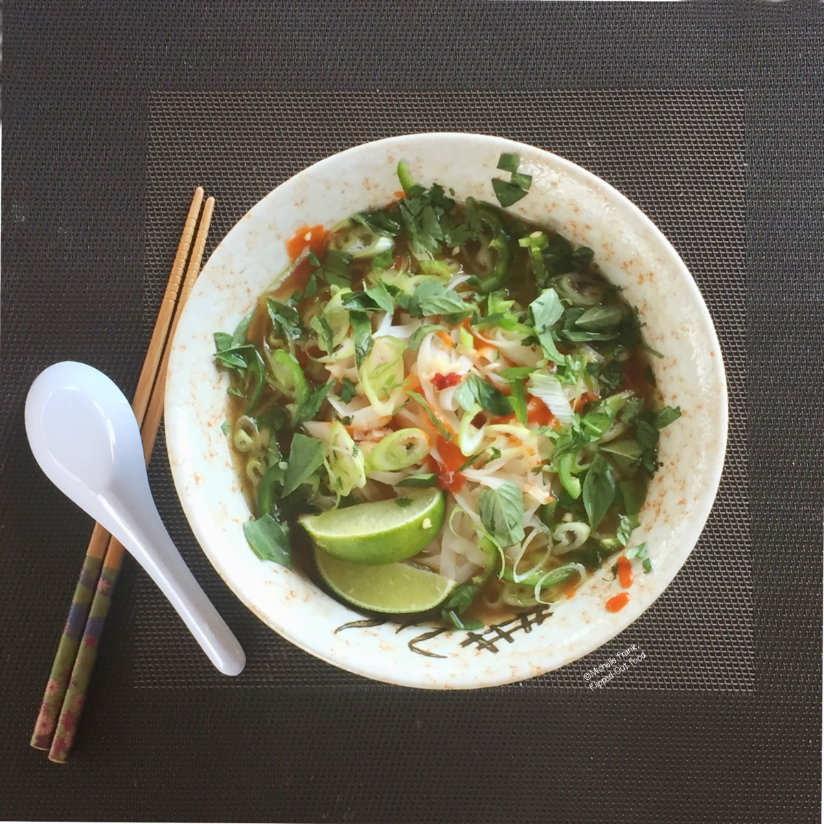 Pressure Cooker Pho Ga in a ceramic bowl sitting atop a woven placemat next to a pair of chopsticks and a spoon. The pho is piled high with herbs and aromatics, with two lime wedges and sriracha.