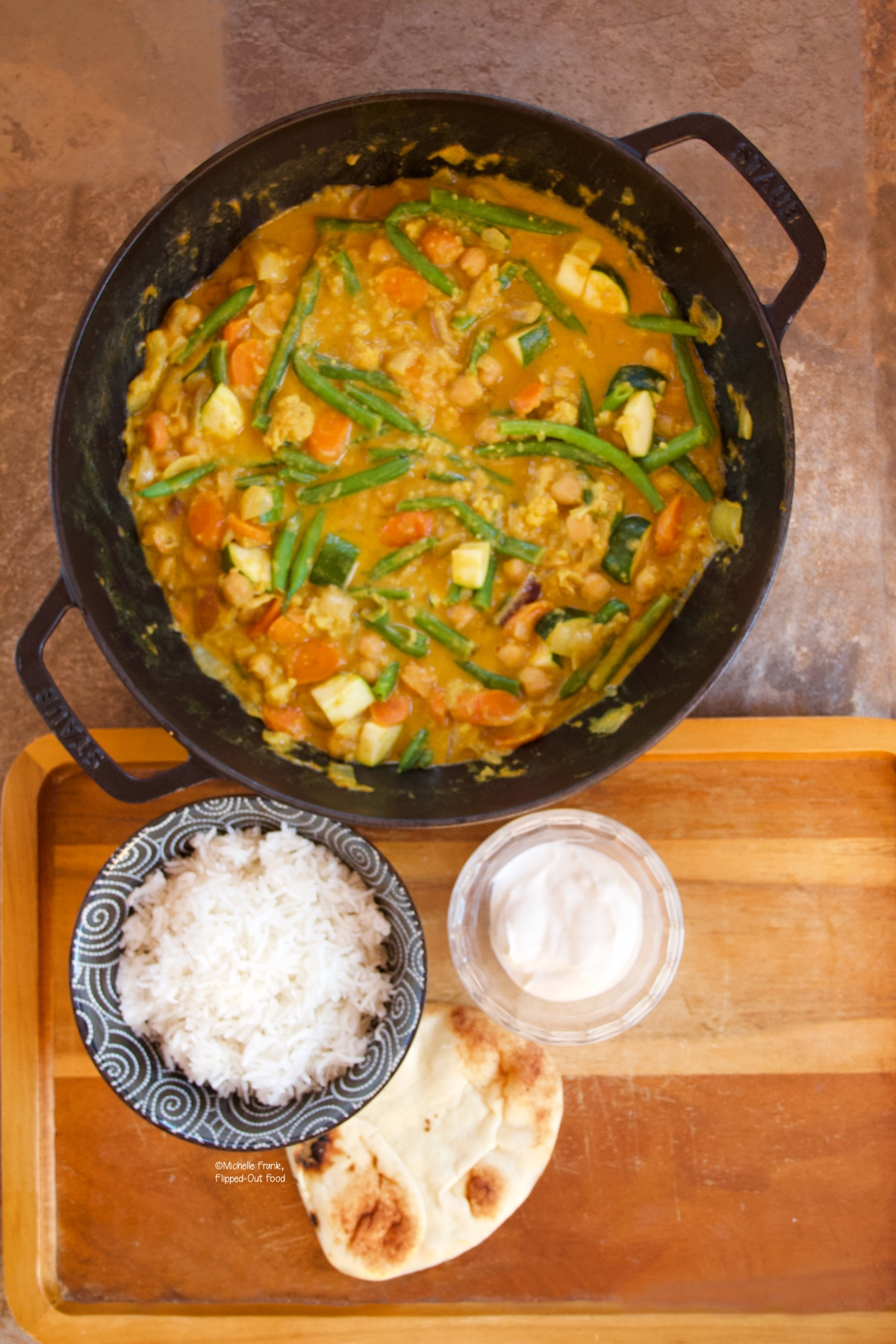 Easy Red Vegetable Curry in a cast-iron wok next to a bowl of rice, a pita, and a ramekin of Greek yogurt.