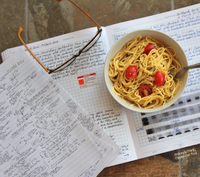 A serving of Healthy MIcrowave Dorm Room Pasta with sliced grape tomatoes. The bowl sits on top of a lab notebook next to an unoccupied pair of glasses.