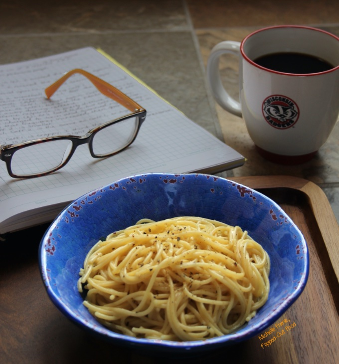 A serving of Healthy Microwave Dorm Room Pasta (plain, with only grated Parmesan and black pepper) in a blue bowl. The bowl sits in front of a lab notebook, a pair of glasses, and a coffee cup with the Bucky Badger logo (on Wisconsin!).
