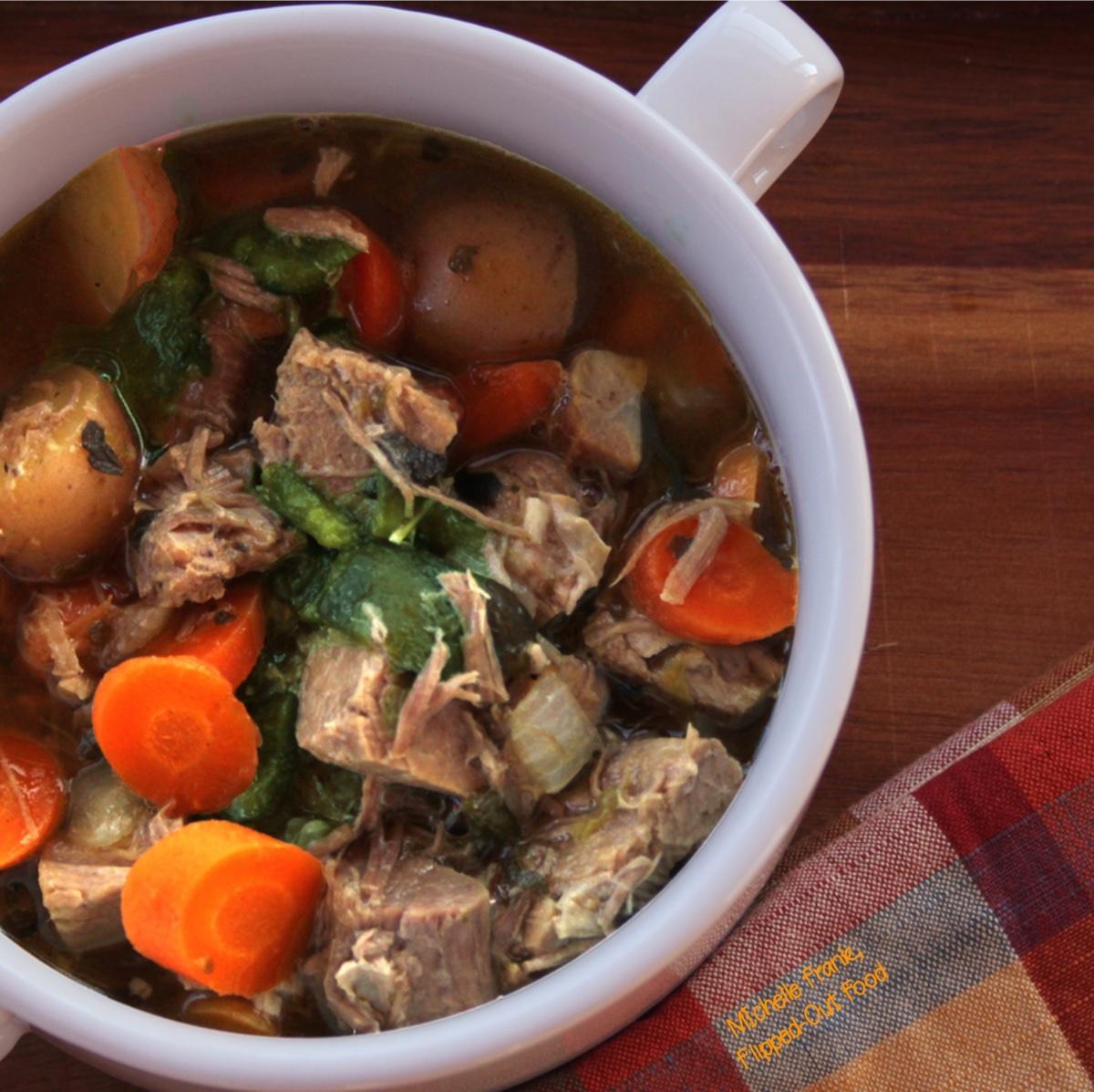 A closeup of Caldillo: Green Chile Pork Stew in a 2-handled bowl.