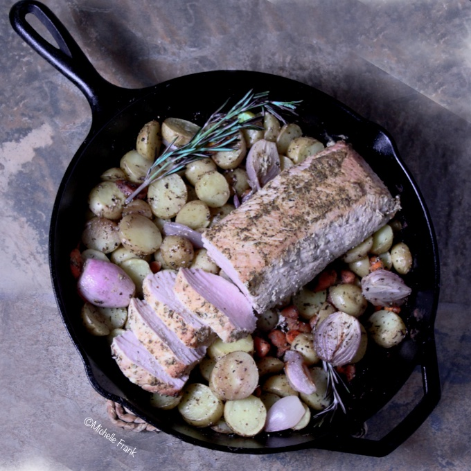 One-skillet mustard-herb-crusted roast pork tenderloin, fresh out of the oven, partly sliced and garnished with rosemary sprigs..