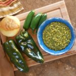 A rotated view of fresh salsa verde in a blue bowl sitting atop a wooden cutting board, surrounded by poblano and jalapeno peppers and an onion. A colorful, striped cloth sits off to one side.