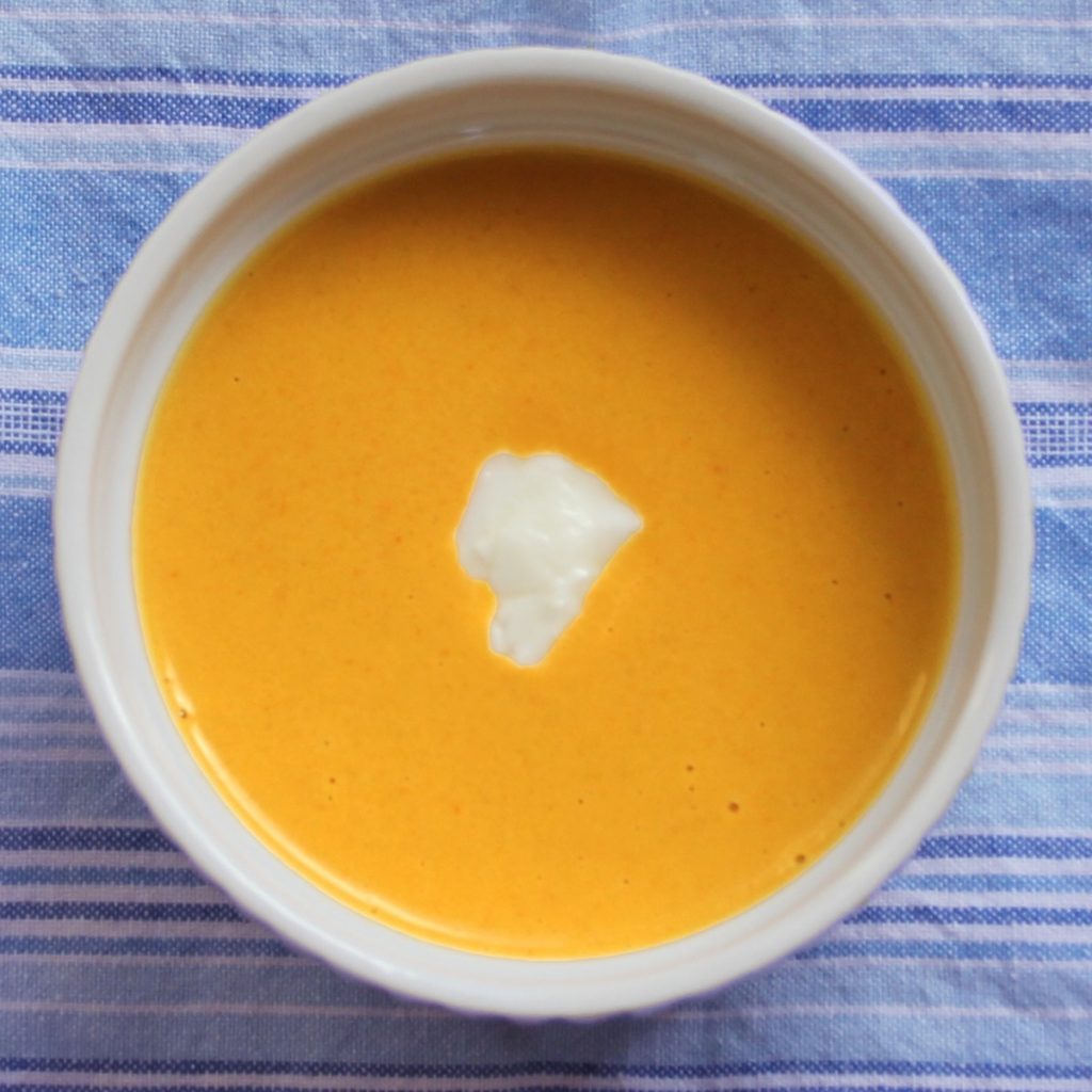 Overhead of curried acorn squash soup in a white bowl set atop a blue and white striped cloth.