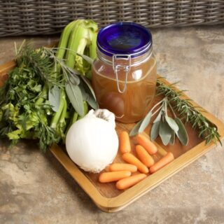 Crockpot Turkey Stock in a blue-capped Mason jar. Surrounded by herbs, carrots, onion, garlic, and celery.