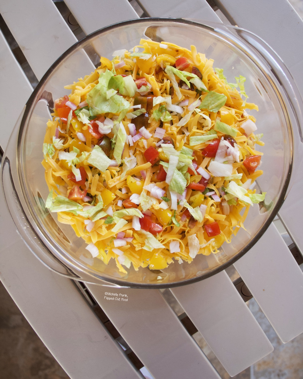 Phil's Taco Dip party appetizer in a clear pyrex serving dish.