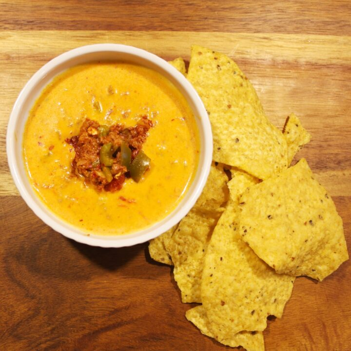 Chile con Queso Dip in a white bowl, served with tortilla chips.