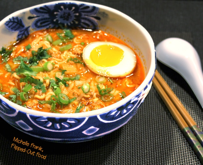 pork-miso ramen soup with soy-marinated egg in beautiful blue bowl, side angle