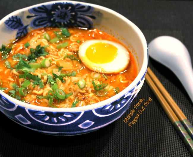 pork-miso ramen soup with soy-marinated egg side-view in pretty blue bowl