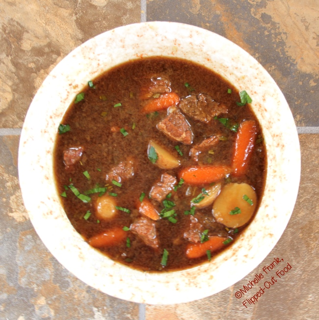 This is a heaping serving of Make-Ahead Irish Guinness Stew sprinkled with parsley. The rich, complex broth is the result of beef slowly simmering in Guinness Stout, along with a few other flavor-building hacks. |Irish Food | Comfort Food | Guinness Stew | Beef Stew | Lamb Stew