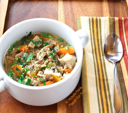 barley chicken vegetable soup on a tray with striped napkin and soup spoon