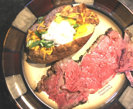A serving of Date Night Prime Rib for 2 with a loaded baked potato on the side. #primerib #primeribroast #holidaydinner #datenight #datenightdinner #valentinesdaydinner via @FlippedOutFood