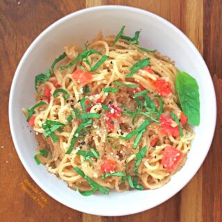 Easy garlic-tomato-basil pasta serving on wood background