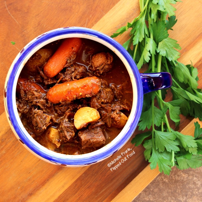 A heaping serving of Make-Ahead Irish Guinness Stew in a one-handled blue and white bowl. The stew is loaded with carrots, potatoes, and fall-apart tender meat. The rich, complex broth is the result of beef slowly simmering in Guinness Stout, along with a few other flavor-building hacks. |Irish Food | Comfort Food | Guinness Stew | Beef Stew | Lamb Stew