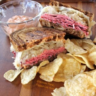 Side view of Best-Ever Reuben Sandwiches served with 1000 island dressing on the side in a clear ramekin and a serving of chips. #reubensandwich #saintpatricksday #stpaddysday #cornedbeef #pubfood #sandwich via @flippedoutfood