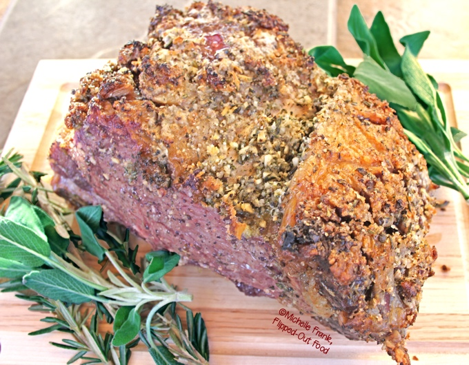 Date night prime rib for 2 resting on the cutting board with fresh herbs. #primerib #primeribroast #holidaydinner #valentinesdaydinner #datenight #romanticfood via @FlippedOutFood