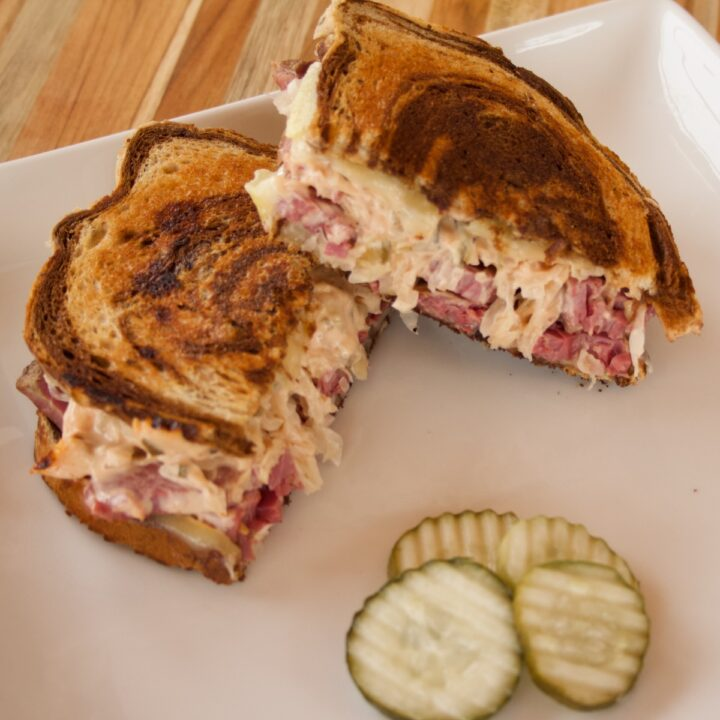 A Reuben Sandwich on marbled rye, sliced in half on a serving plate with pickle slices.