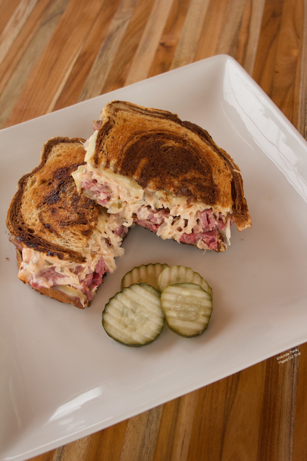 A Reuben sandwich, sliced in half, on a white plate garnished with pickle slices.