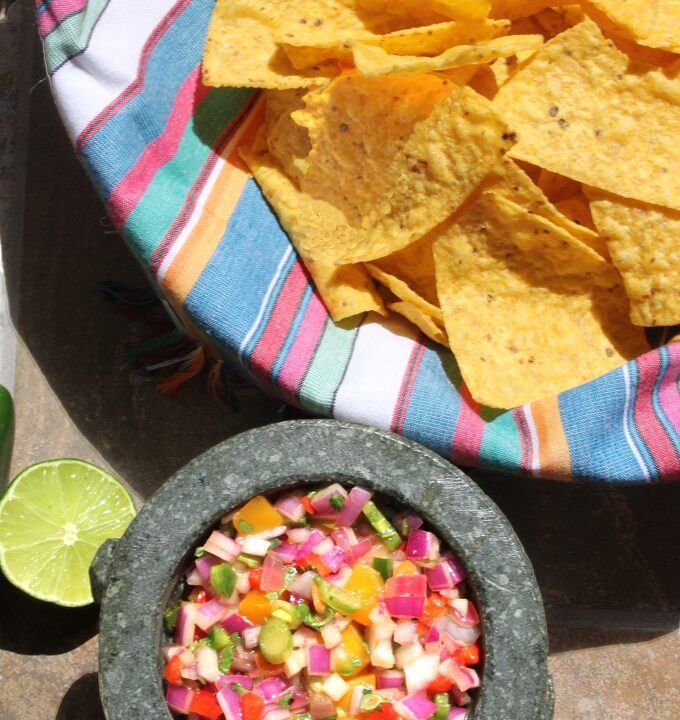 Fiery Mango-Habanero Salsa in molcajete with tortilla chips and lime. #salsa #mexicanfood #partydip #spicyfood #flippedoutfood @FlippedOutFood
