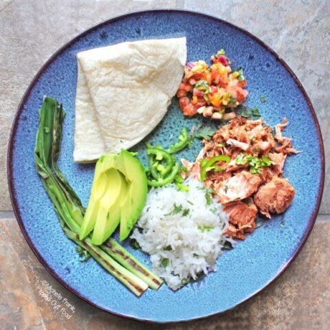 Slow-cooker mojo carnitas taco bar with mango-habanero salsa, warm tortilla, avocado, charred scallions, and rice. #mexicanfood #carnitas #slowcooker #crockpot #cincodemayo @FlippedOutFood