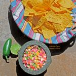 fiery mango-habanero salsa in molcajete with tortilla chips, lime, and jalapeno